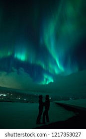 Aurora and hugging couple. Night winter landscape . Northern lights at Iceland.