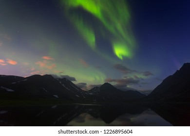 Aurora in the night sky cut the mountains. Yamal. Russia
