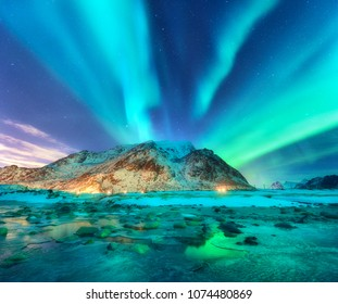 Aurora. Northern lights in Lofoten islands, Norway. Starry sky with polar lights. Night winter landscape with aurora, sea with sky reflection, stones, sandy beach and mountains. Green aurora borealis