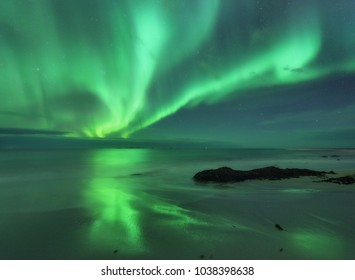 Aurora on the sea. Northern lights in Lofoten islands, Norway. Starry sky with polar lights. Night landscape with aurora, sea with blurred water and sky reflection, stones, sandy beach.Aurora borealis