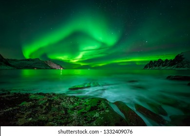 Aurora over Ersfjord and Tugeneset rocky coast with mountains in background, Norway