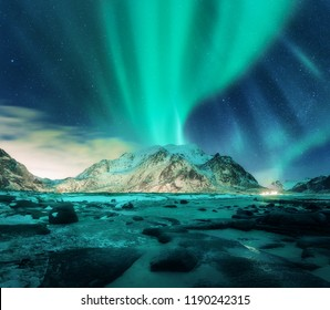 Aurora over snowy mountains, sandy beach with stones. Northern lights in Lofoten islands, Norway. Starry sky with polar lights. Night winter landscape with green aurora borealis, rocks, illumination