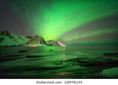 Aurora over Tugeneset rocky coast with mountains in background, Senja, Norway