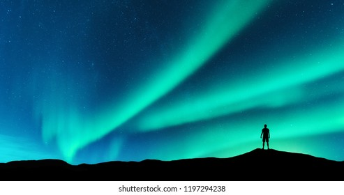 Aurora and silhouette of alone standing man on the hill. Lofoten islands, Norway. Aurora borealis and young man. Sky with stars and green polar lights. Night landscape with northern lights. Concept