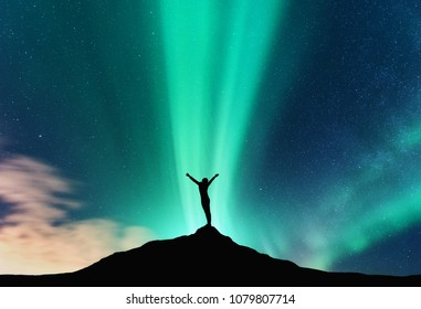 Aurora and silhouette of standing woman with raised up arms on the mountain in Norway. Aurora borealis and happy girl. Starry sky, green polar lights. Night landscape. Northern lights. Travel