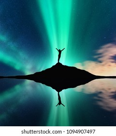Aurora and silhouette of a woman with raised up arms on the mountain. Night landscape with aurora borealis, happy girl, stars, green polar lights, lake, sky reflection in water. Northern lights.Norway