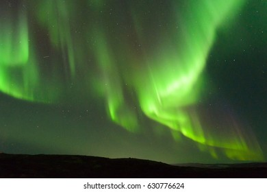 The Aurora in the sky above the hills at night . Horizontal .