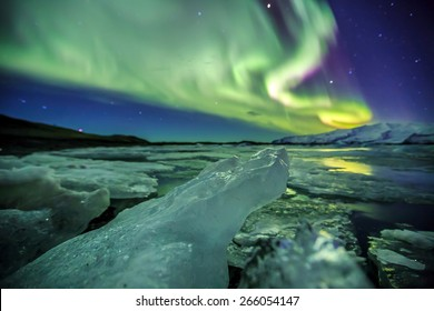 Auroral display over the glacier lagoon Jokulsarlon in Iceland.