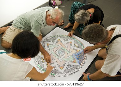 AUROVILLE, INDIA - December 2016: Coloring a mandala together in an art gallery