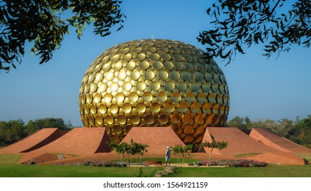 AUROVILLE,PUDUCHERRY (PONDICHERRY)/INDIA-FEBRUARY 26 2018:A groundsman tends an area in front of the golden globe of Matrimandir or  Mother Temple, which stands as the spiritual center of Auroville.