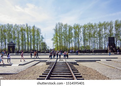 Auschwitz, Auschwitz/Poland - 04.20.2019: Railway tracks and people near Holocaust memorial in Auschwitz II - Birkenau Concentration and Extermination Camp, Oswiencim, Poland