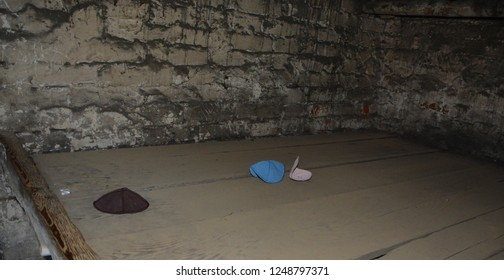 AUSCHWITZ BIRKENAU POLAND 09 17 17: Kippas in Auschwitz concentration camp inside barrack wall of German Nazi concentration camps and extermination camps built and operated by the Third Reich.