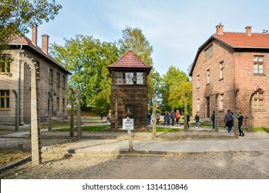 Auschwitz, Birkenau. Poland. September 2018. Visitors in concentration camp. Tourists Taking Photos at Auschwitz Concentration Camp with Arbeit Macht Frei Entrance Gate. museum honoring the victims.