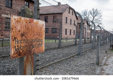 Auschwitz, Poland. April 2018. Inside the German Concentration Camp of Auschwitz I, showing high voltage warning sign against the barbed wire fence with barrack buildings in the background.