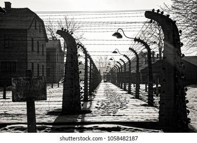 AUSCHWITZ, POLAND - JANUARY 26, 2018 ; Museum Auschwitz - Birkenau. Warning sign high voltage. Barbed wire around a concentration camp.