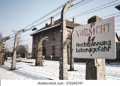 AUSCHWITZ, POLAND - JANUARY 28, 2017 ; Museum Auschwitz - Birkenau. Warning sign high voltage. Barbed wire around a concentration camp.