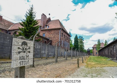 "AUSCHWITZ, POLAND - July 3, 2017.Barracks with barbed wire in a concentration camp in Auschwitz (Poland).Museum Auschwitz - Birkenau. Barracks with barbed wire and ""HALT! STOJ"" stop sign."