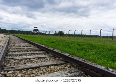 Auschwitz, Poland - June 30 2018: The railroad track at concentration camp. Watchtower and fence on the background.