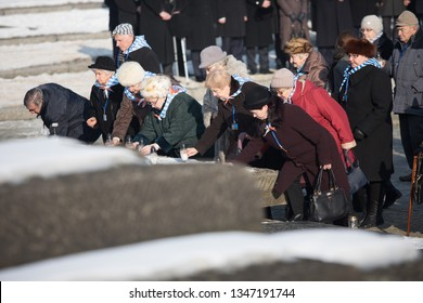 Auschwitz-Birkenau, Poland - 27 January 2017: 72 th Anniversary of the Liberation of Auschwitz. Survived prisoners of the german concentration camp Auschwitz-Birkenau light candles at the monument