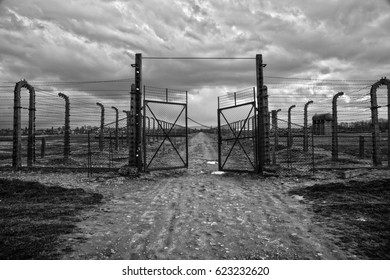 AUSCHWITZ-BIRKENAU, POLAND - APRIL 18, 2017 ; Museum Auschwitz - Birkenau. Holocaust Memorial Museum.  Barbed wire and fance around a concentration camp. Side entrance of the concentration camp.