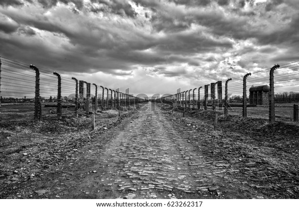 AUSCHWITZ-BIRKENAU, POLAND - APRIL 18, 2017 ; Holocaust Memorial Museum.  Barbed wire and fance around a  camp. Side entrance of the concentration camp. Road of dead for deportation prisoners.