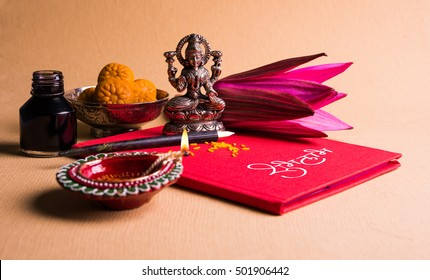 An auspicious Indian writing Shubha Labh means Goodness & Wealth, over Red accounting note book / bahi khata with goddess Laxmi idol, diya, sweets, lotus, pen with ink on Laxmi pujan, Diwali Festival
