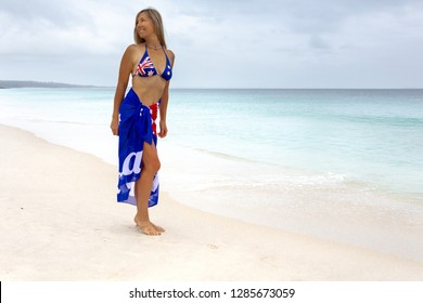 Aussie beach woman barefoot, smiling, looking over her shoulder.   She has a flag draped around her showing a little bit of leg and wearing a flag embossed bikini top.  Australia Day, travel or touris