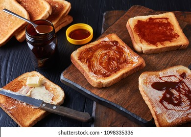aussie savory toasts for breakfast with butter and marmite - a thick Australian healthy food spread made from leftover brewers yeast extract with vegetables and spices, view from above, close-up