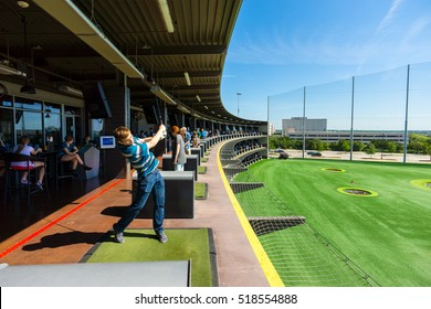 AUSTIN - CIRCA APRIL 2016: A man hits a golf ball at a Top Golf golfing complex.