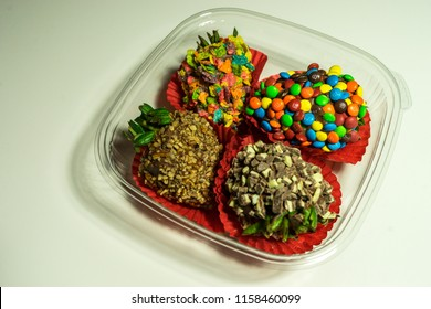 AUSTIN- CIRCA APRIL 2018: Candy and M&M coated hand dipped strawberries sit in a tray on a white table ready to be eaten. These strawberries are a popular treat on Valentine's day and Mother's day.