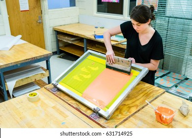 AUSTIN - CIRCA FEBRUARY 2016: A student at the University of Texas creates a silk screen print during an art class on campus in Austin, Texas