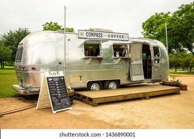AUSTIN - CIRCA MAY 2019: People drink coffee at a local food truck called Compass Coffee in east Austin, Texas. The food truck serves a wide variety of coffee drinks.