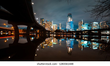 Austin skyline at night and Lamar pedestrial Bridge with bright illuminated buildings reflecting in Lady Bird Lake