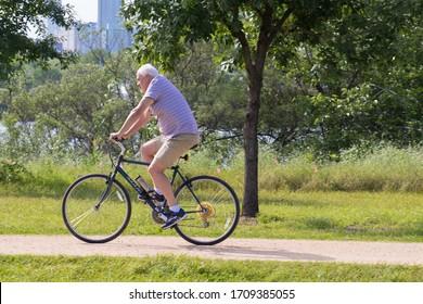 Austin, Texas - 16 April 2020: a older man enjoying a leisurely bike ride on a gravel trail