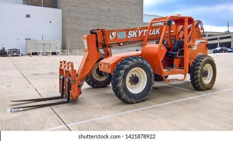 Austin, Texas - 23 May 2017: an orange Skytrak 6036 telehandler forklift beyond a building