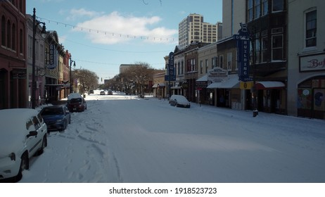 Austin, Texas - February 15, 2021: Snow covers a frozen 6th street in the downtown nightlife district