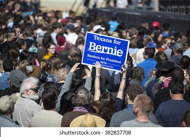 AUSTIN, TEXAS - FEBRUARY 27, 2016: A woman holds up a Texans For Bernie sign while awaiting the arrival of Senator Bernie Sanders at a campaign rally at the Circuit of the Americas.
