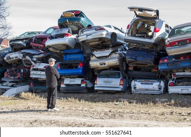 AUSTIN, TEXAS - JANUARY 3 2017 a man viewing stacked vehicles in a junkyard