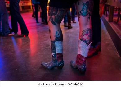 Austin, Texas - June 13, 2014: Detail of the boots and tattoed legs of a young woman in the Broken Spoke dance hall in Austin, Texas, USA