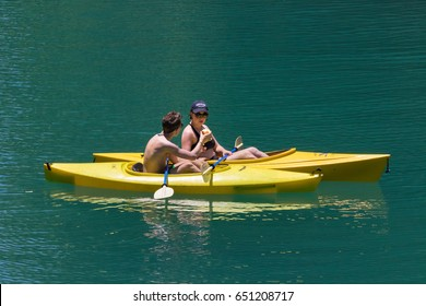 AUSTIN, TEXAS - MAY 25 2017: contrasting yellow kayaks with green water while sharing food