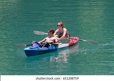 AUSTIN, TEXAS - MAY 25 2017: a young man and woman in a red white and blue plastic kayak