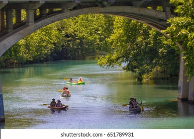 AUSTIN, TEXAS - MAY 25 2017: two canoes three kayaks and an arched bridge