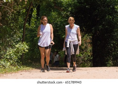 AUSTIN, TEXAS - MAY 25 2017: two young women walking and talking on a trail