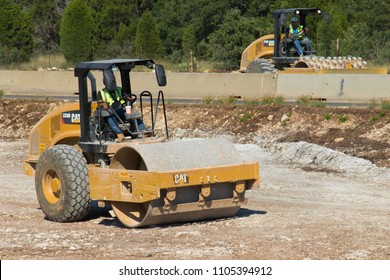 AUSTIN, TEXAS - MAY 29 2018: two Caterpillar CS56B vibratory soil compactors on opposite sides of a hiway preparing the ground