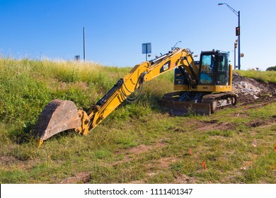 AUSTIN, TEXAS - MAY 29 2018: a Caterpiller 314E L CR hydraulic excavator at rest next to a small slope