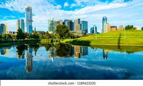 Austin Texas mirrored reflection of Perfect symmetry and dramatic glass like reflection on water. Skyline Cityscape view from Butler Park green hills and tall towers rise above Downtown Capital Cities