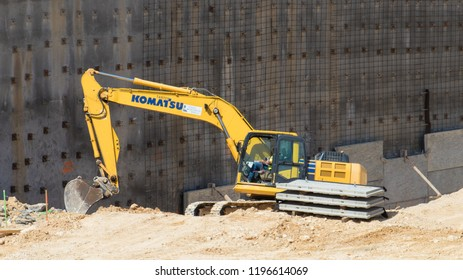 AUSTIN, TEXAS - OCTOBER 4 2018: a Komatsu hydaulic excavtor digging next to a wall