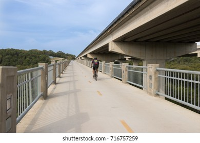 AUSTIN, TEXAS - SEPTEMBER 13 2017: a male cyclist climbing up from a creek bed on a dedicated bike and pedestrian bridge