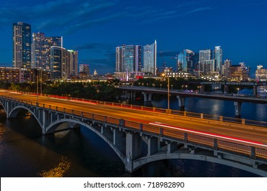 The Austin, Texas skyline from above Lady Bird Lake featuring the Lamar Bridge during sunset.