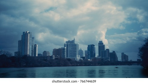 The Austin, Texas skyline is prominent in front of a flurry of clouds on this mostly cloudy day.  Lady Bird Lake is also featured in the foreground.